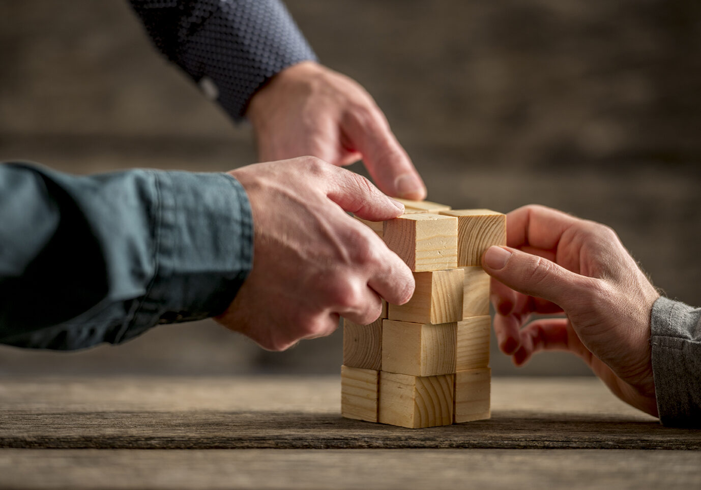 Hands of three people building a tower of wood blocks on a table, teamwork concept.