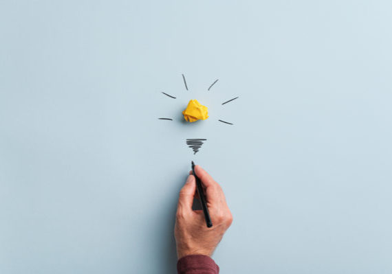 Male hand drawing a light bulb over blue background in a conceptual image.