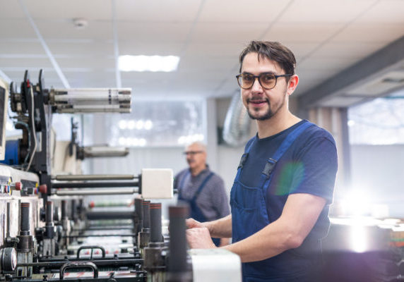 Portrait of content young printing specialist in glasses standing at printing press